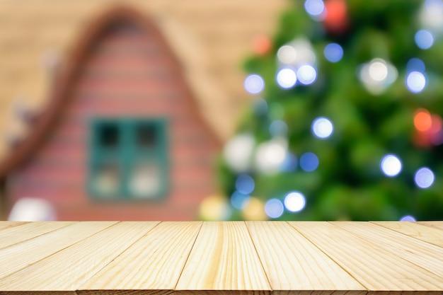 Leere holztischplatte mit abstraktem unschärfe-weihnachtsbaum mit dekorations-bokeh-lichthintergrund für produktpräsentation