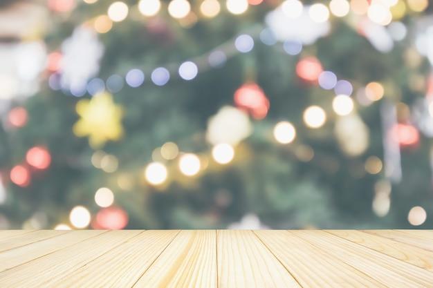 Leere holztischplatte mit abstraktem unschärfe-weihnachtsbaum mit dekorationsbokeh-lichthintergrund für produktanzeige