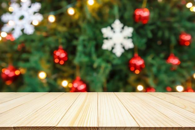 Leere holztischplatte mit abstrakter unschärfe-weihnachtsbaum mit dekorations-bokeh-lichthintergrund für produktanzeige