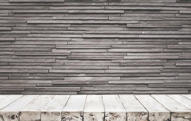 Leere holztischplatte mit backsteinmauerhintergrund