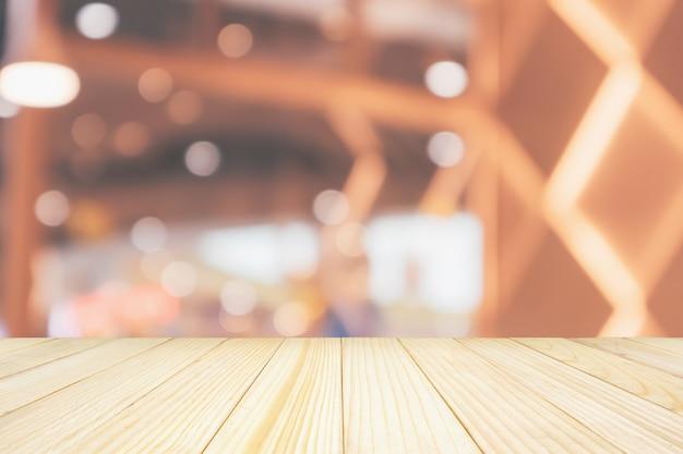 Leere holztischplatte mit café-restaurant mit abstraktem bokeh beleuchtet defokussierten unschärfehintergrund