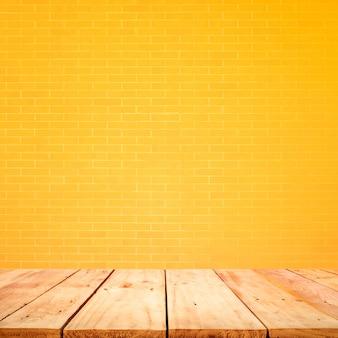 Leere holztischplatte mit gelbem backsteinmauerhintergrund. zum erstellen der produktanzeige oder des entwurfs des visuellen layouts des schlüssels
