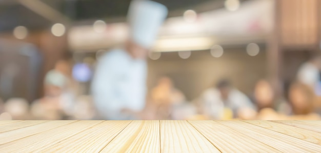 Leere holztischplatte mit küchenchef, der in der restaurantküche kocht, verschwommener defokussierter hintergrund