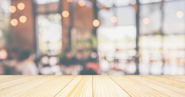 Leere holztischplatte mit restaurantcafé oder coffeeshop-innenausstattung mit kunden