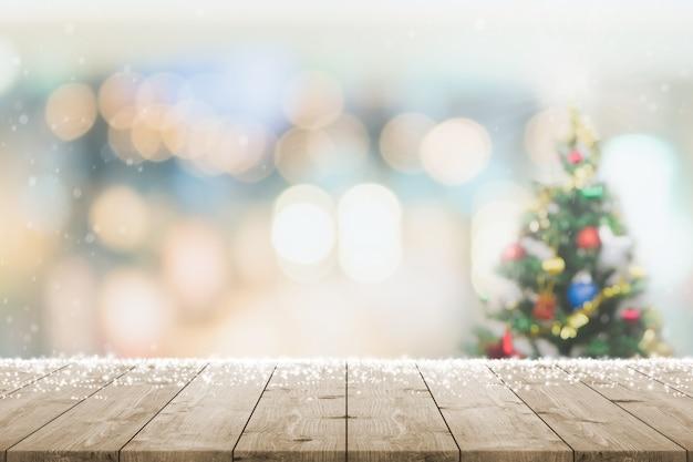 Leere holztischplatte mit unscharfem bokeh-weihnachtsbaum und neujahrsdekorationsbannerhintergrund mit schneefall - kann für die anzeige oder montage ihrer produkte verwendet werden.
