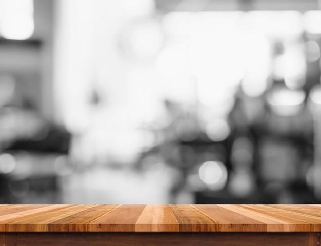 Leere holztischplatte mit unscharfem schwarzweiss-caféhintergrund