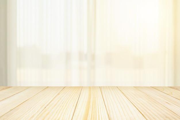 Leere holztischplatte mit unscharfem weißem vorhangfenster und grünem gartenhintergrund für produktanzeigevorlage