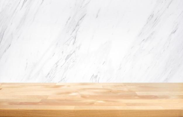 Leere holztischplatte mit weißem marmorwandhintergrund.