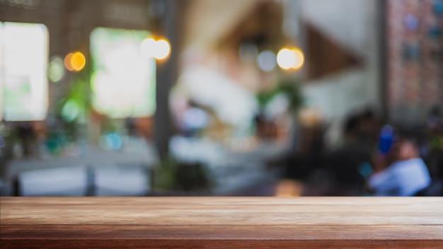 Leere holztischplatte und unscharfer coffeeshop-, café- und restaurantinnenhintergrund.