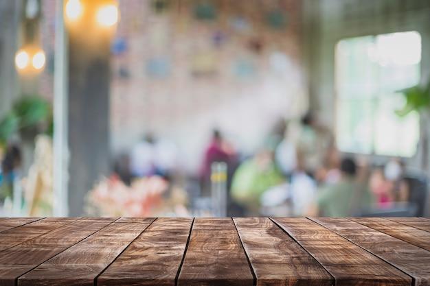 Leere holztischplatte und unscharfer coffeeshop- und restauranthintergrund.