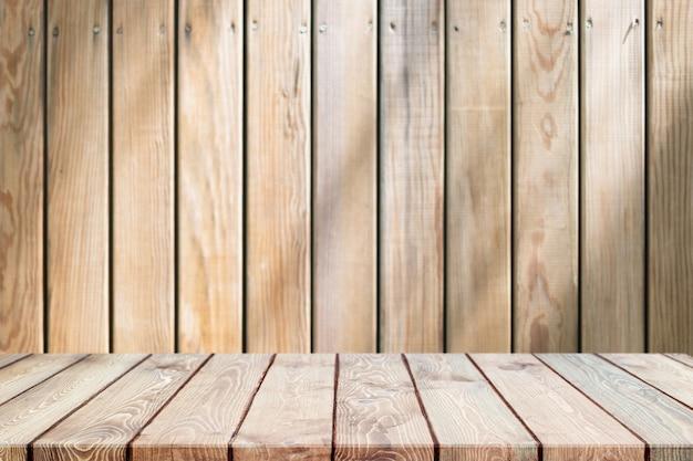 Leere holztischplatte und verschwommene holzwand im gartenhintergrund mit blätterschatten - kann für die anzeige oder montage ihrer produkte verwendet werden.