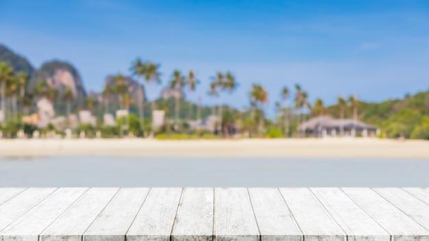 Leere holztischplatte und verschwommener sommerstrand im tropischen resort-bannerhintergrund - kann für die anzeige oder montage ihrer produkte verwendet werden.