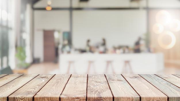 Leere holztischplatte und verschwommenes café, café und restaurantinnenhintergrund.