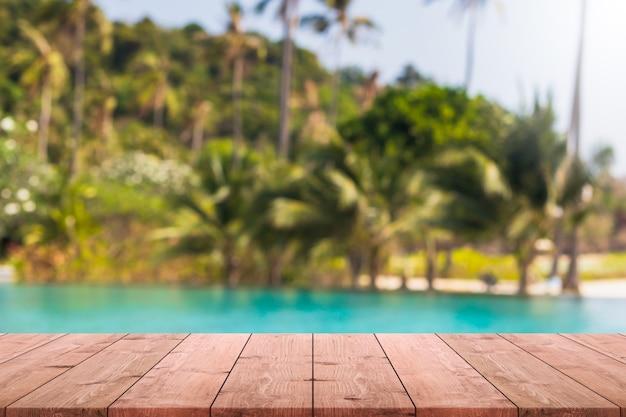 Leere holztischplatte und verschwommenes schwimmbad im tropischen resort im sommerfahnenhintergrund.