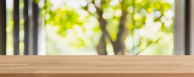 Leere holztischplatte und verschwommenes wohnzimmer im innenbereich mit grünem baum außerhalb des fensterhintergrunds. - kann für die anzeige oder montage ihrer produkte verwendet werden.