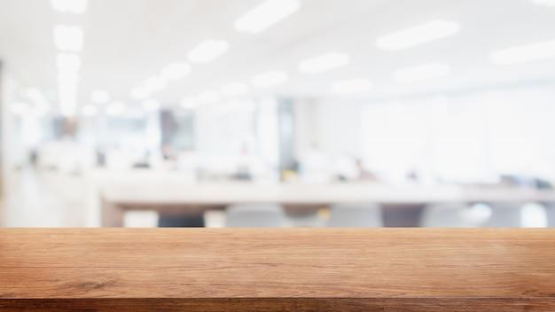 Leere holztischplatte und verwischen den hintergrund des modernen bürogebäudes.
