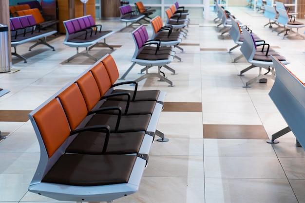 Leere internationale flughafengebäude während der pandemie. leere sitzreihen in der flughafenlounge