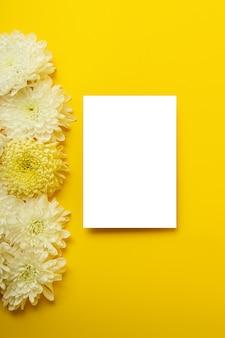 Leere isolierte weiße karte auf dem kräftigen gelben hintergrund mit schönen chrysanthemen im hintergrund