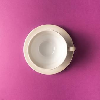 Leere kaffee- oder teeschale auf purpurrotem farbhintergrund, kopienraum.