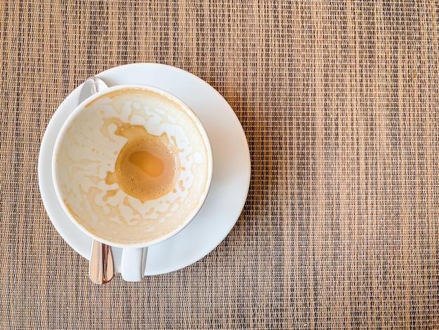 Leere kaffeetasse auf hölzernem schreibtisch auf draufsicht.