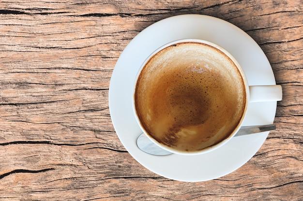 Leere kaffeetasse nach getränkschaum in der weißen schale auf altem holztisch