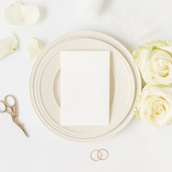Leere karte auf keramikplatte mit rosen; schere und eheringe auf weißem hintergrund