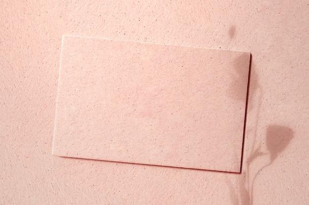 Leere karte auf rosa beton