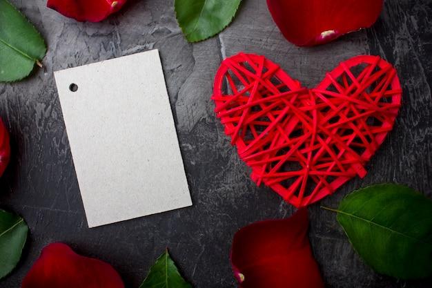 Leere karte für eine unterschrift unter den blättern einer rose und eines roten herzens auf einem dunklen hintergrund. valentinstag oder hochzeit. sicht von oben