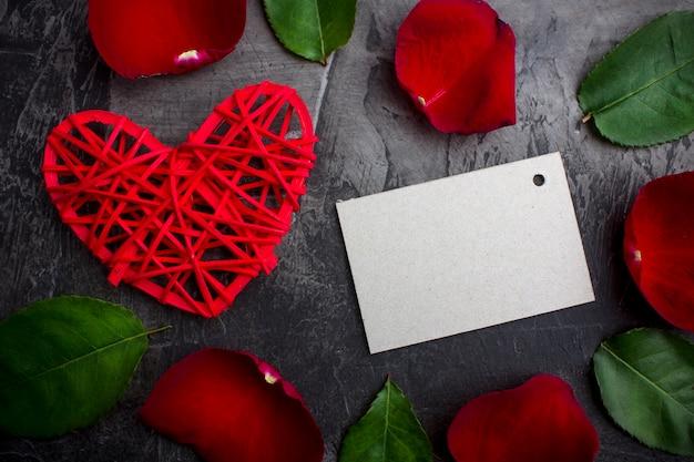 Leere karte für eine unterschrift unter den blüten einer rose und eines roten herzens auf einem dunklen hintergrund. valentinstag oder hochzeit. sicht von oben