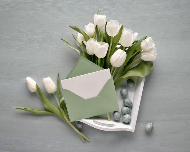 Leere karte im papierumschlag mit dem bündel von weißen tulpen auf dekorativem behälter mit ostereiern