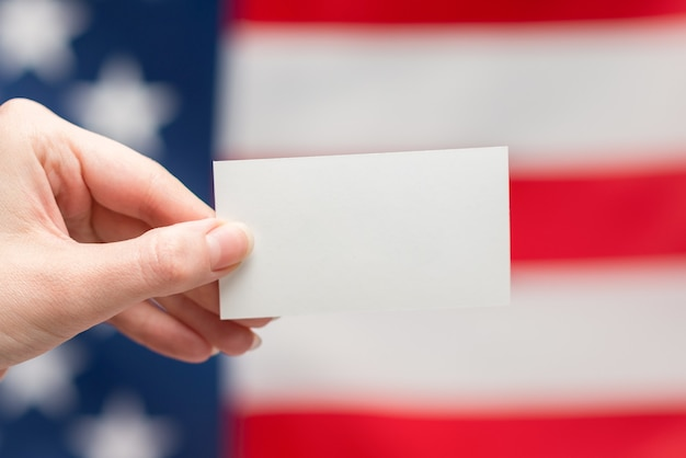 Leere karte in der frauenhand. platz kopieren. oberfläche der amerikanischen flagge