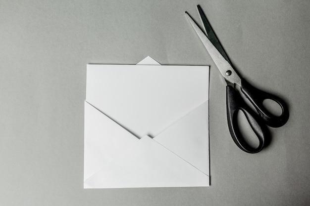 Leere karte in weißem umschlag und schere