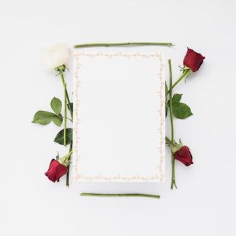 Leere karte mit roten und weißen rosen auf weißem hintergrund
