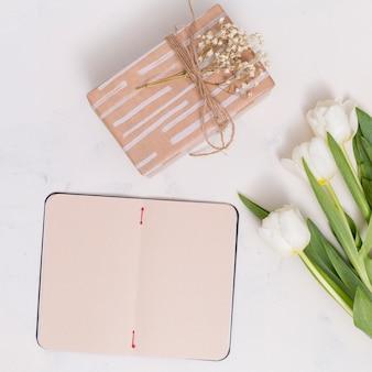 Leere karte öffnen; geschenkbox mit tulpenblumen auf weißem hintergrund