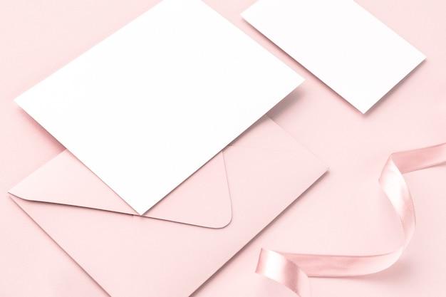 Leere karte und umschlag auf rosa hintergrund