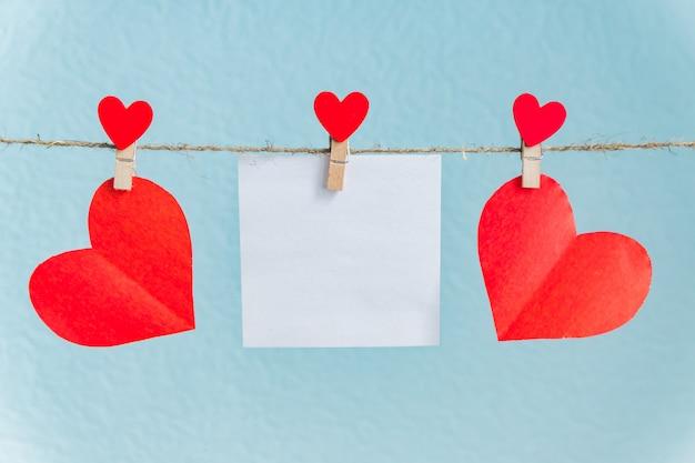 Leere karten von den stiften mit roten herzen. text und blauer hintergrund für valentinstaggrüße