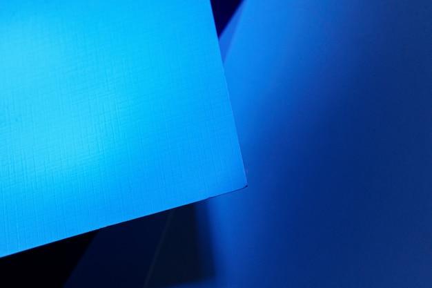 Leere kartonpapierblätter in dunkelblauem licht
