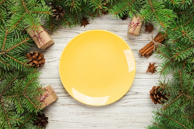 Leere keramische platte auf holztisch mit tannenbaum- und kiefernkegeln