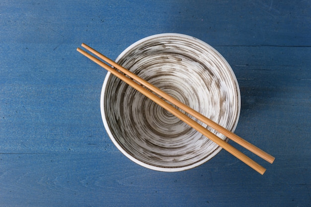 Leere keramische schüssel mit essstäbchen