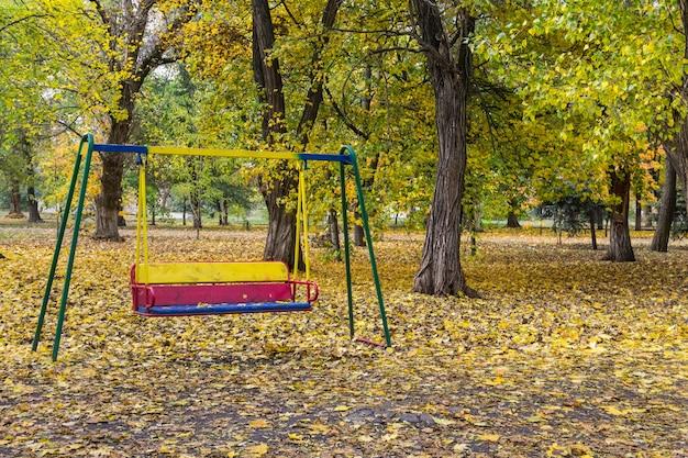 Leere kinderschaukel im stadtpark im herbst