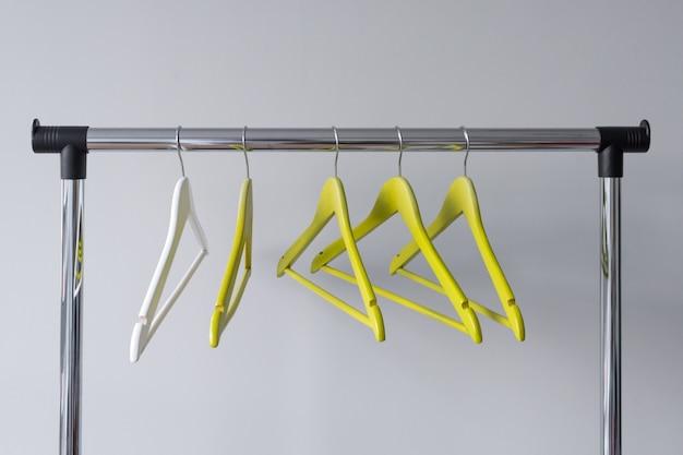 Leere kleiderbügel auf metallschiene auf grau