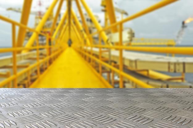 Leere kontrolleureisen-plattenspitze mit offshoreanlage-unschärfehintergrund