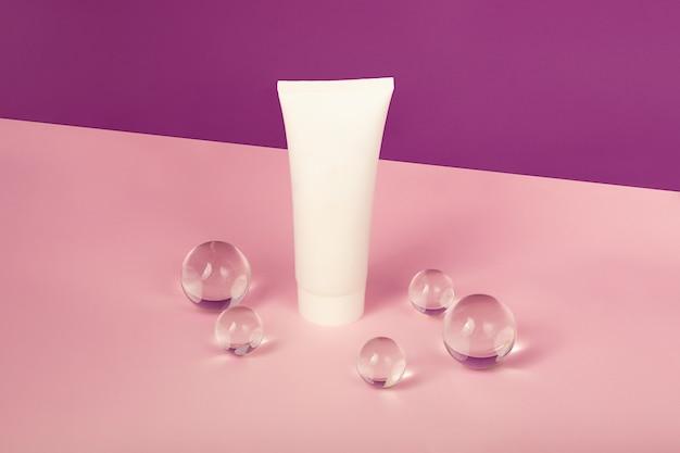 Leere kosmetiktube auf dem rosa und lila isometrischen hintergrund glaskugeln drumherum