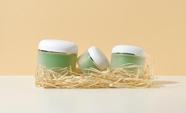Leere kosmetische grüne gläser mit weißen deckeln liegen in holzspänen auf einem weißen tisch, beigefarbenem hintergrund. rohling für branding-produkte creme, gel, serum