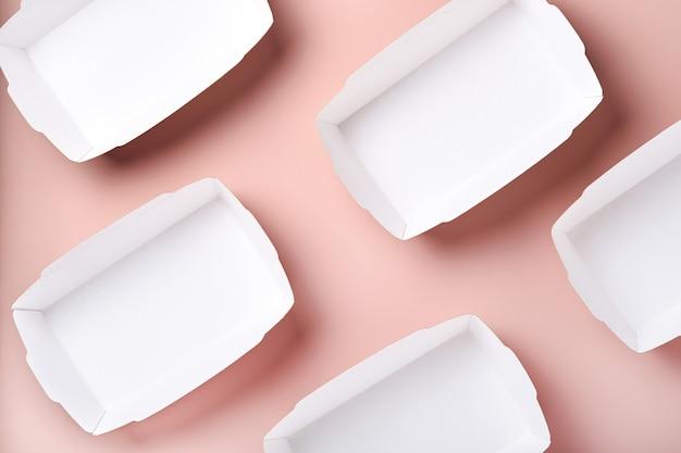 Leere kraftpapierbehälter für lebensmittel oder teller auf rosafarbenem hintergrund. öko-geschirr aus papierhandwerk. recycling- und lebensmittellieferungskonzept. attrappe, lehrmodell, simulation. ansicht von oben, flach.