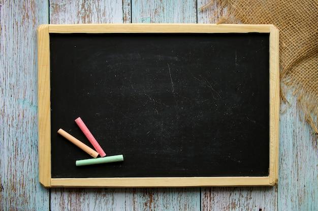 Leere kreidetafel mit kopienraum auf einem gemalten hölzernen hintergrund. farbige kreide. hintergrund für notizen. informationstafel. hochwertiges foto