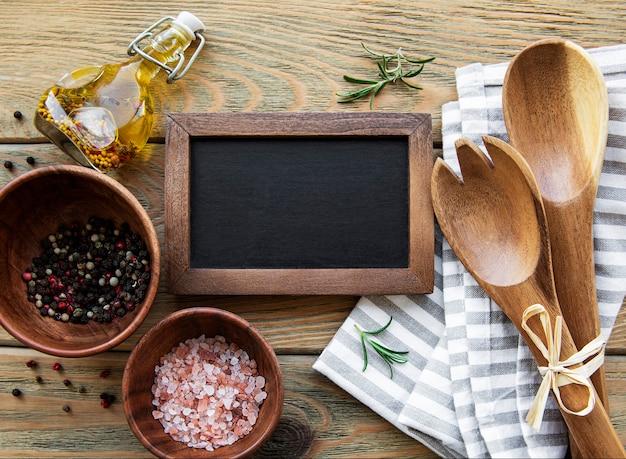 Leere kreidetafel und küchenutensilien mit gewürzen auf einem alten hölzernen hintergrund