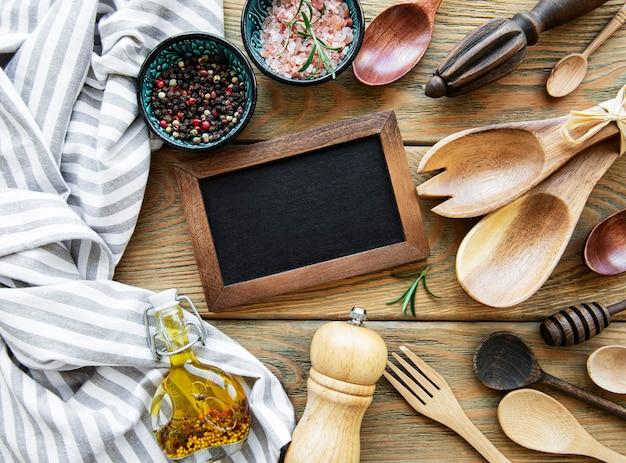 Leere kreidetafel und küchenutensilien mit gewürzen auf einer weißen holzwand