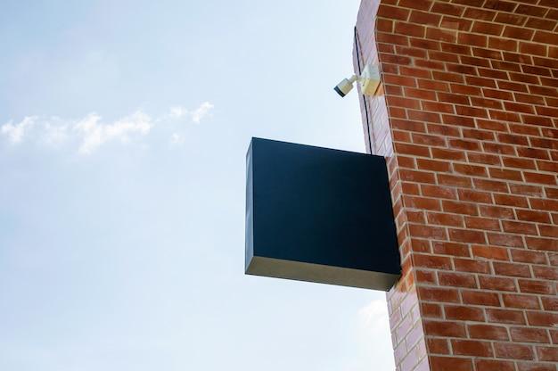 Leere ladenbeschilderung mit cctv-überwachungskamera, die an backsteinmauer und blauem himmel hängt