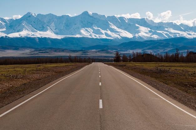Leere landstraße, die zu die berge mit schneekappen führt. altai-gebirgslandschaft